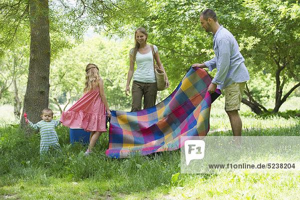 Familie  die Vorbereitung für Picknick auf Wiese