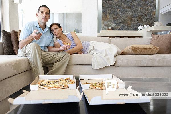 Paar essen Pizza im Wohnzimmer