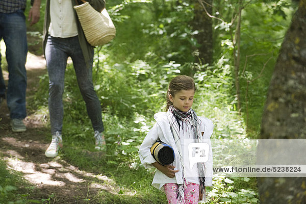 Girl walking in woods with parents