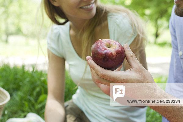Man holding Apple bei Picknick  zugeschnitten
