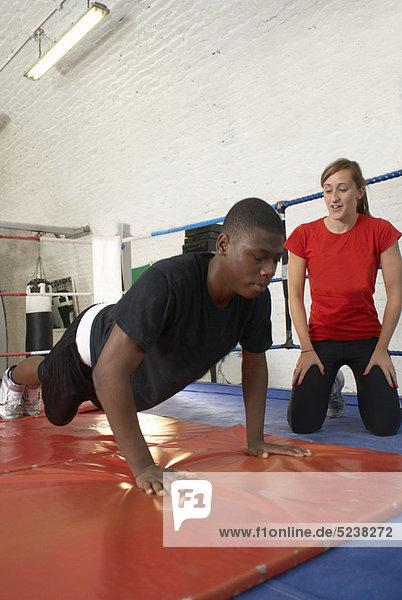 Sportlertraining mit Trainer in der Turnhalle