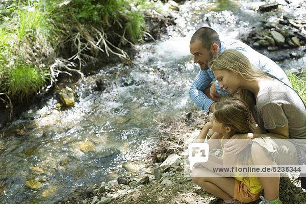 Familie kauerte zusammen neben Stream  Blick auf Wasser