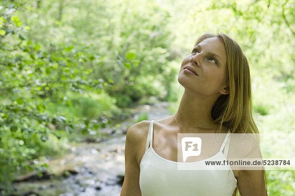 Junge Frau im Freien entspannen  Blick nach oben  in Gedanken