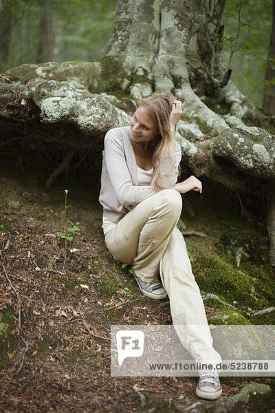 Woman sitting at Baum im Wald