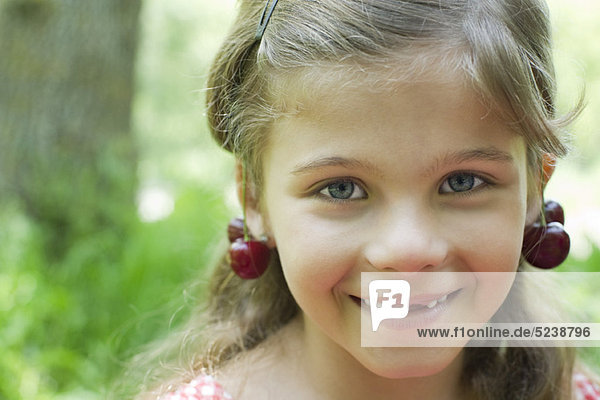 Mädchen mit Kirschen hängen von ihrer Ohren  Porträt
