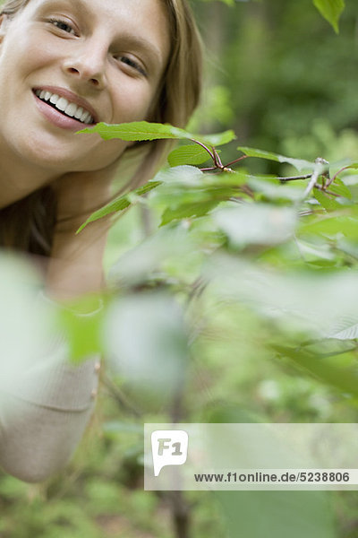 Frau Lächeln in die Kamera hinter Laub  Porträt