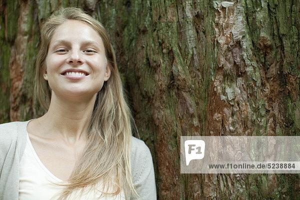 Young Woman leaning gegen Stamm  Porträt