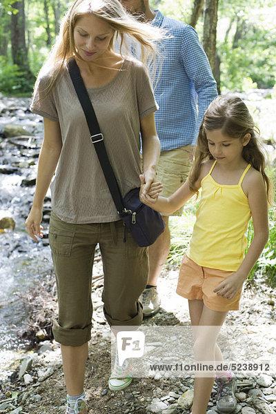 Mutter und Tochter gehen hand in hand im freien