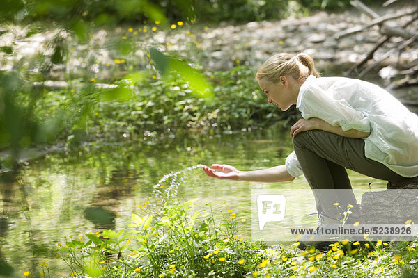 Young woman splashing water by river