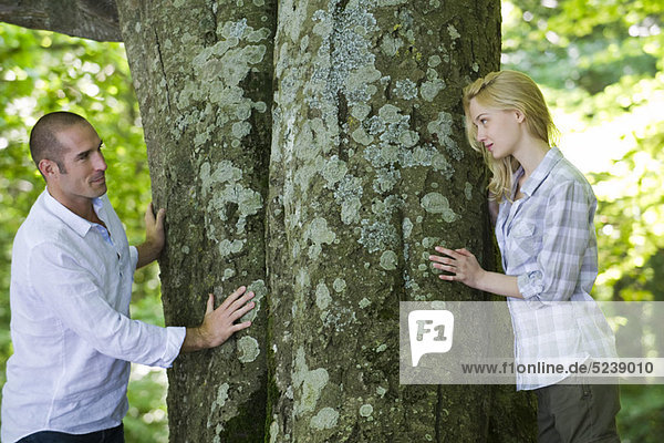 Couple looking at each other around tree trunks