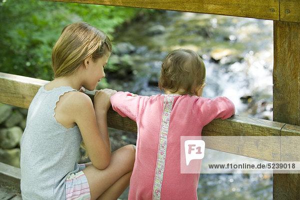 Mädchen und Baby Schwester über Geländer der Brücke bei Stream unten schauen