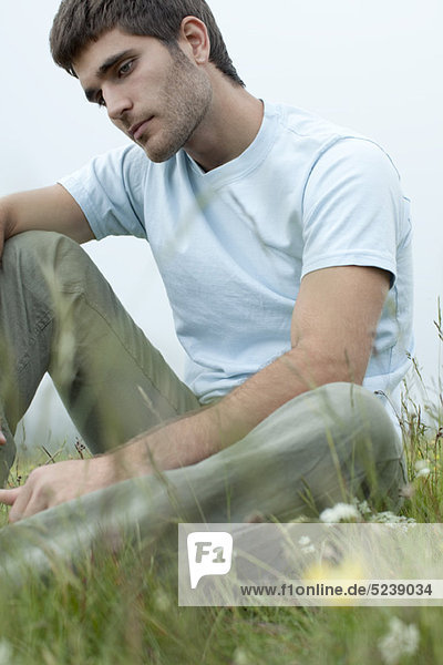 Mann  sitzend auf Wiese im Denken