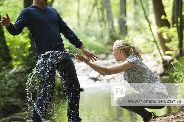 Young woman splashing water at man