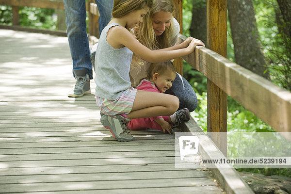 Mutter und zwei jungen Töchtern  die auf der Suche über das Geländer der Brücke zusammen