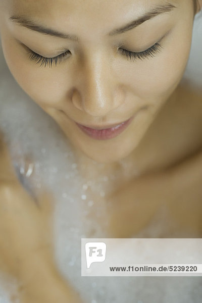 Young woman taking bubble bath  high angle view