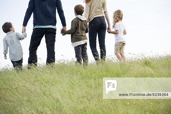 Familie gehen zusammen in Feld  Rückansicht