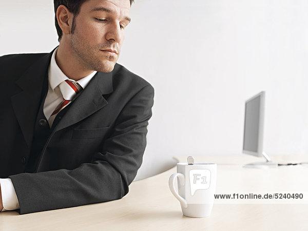 Manager sitzt nachdenlich mit einer Tasse Kaffee am Schreibtisch