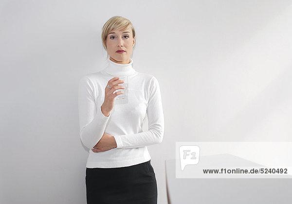 Frau steht in weißem Rolli mit Tasse Kaffee im Büro