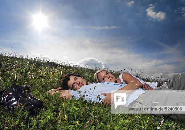 Paar  liegen auf Wiese  Sonne