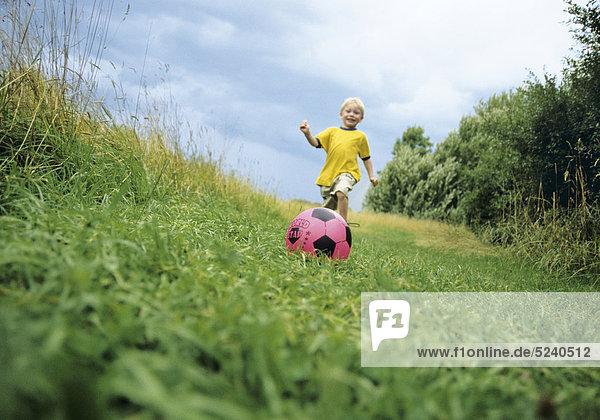 Kleiner Junge spielt auf Wiese Fußball