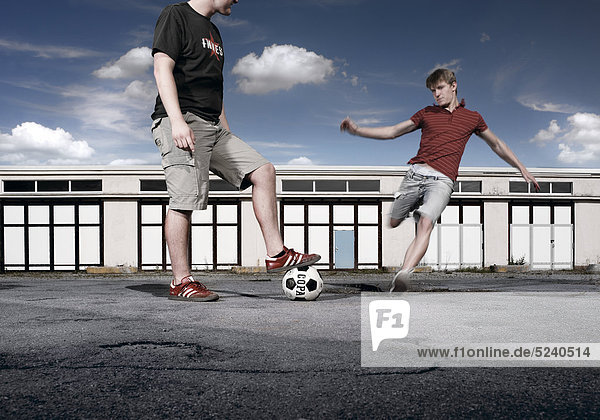 Zwei junge Männer spielen auf Garagenplatz Fußball