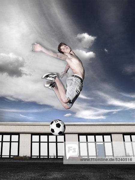 Junger Mann spielt auf Garagenplatz Fußball  Luftsprung