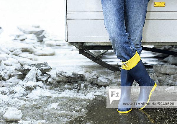 Frau steht mit Gummistiefeln im Schneematsch  Detail Beine