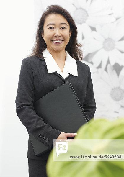 Asiatische Frau mit Aktenmappe im Büro  große grüne Aronstabblüte im Vgr.