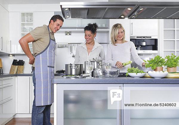 Zwei Frauen und ein Mann in der Küche  er mit Schürze