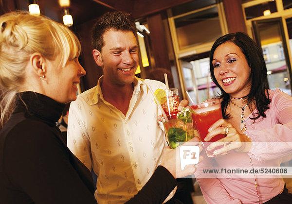 Zwei Frauen und ein Mann stoßen in einer Bar mit Cocktails an