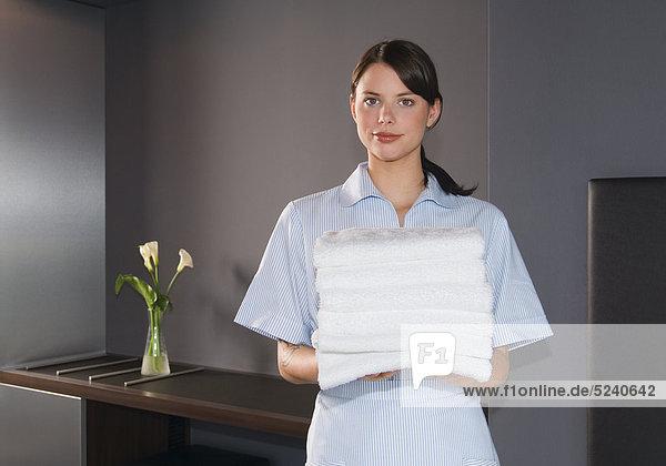 Zimmermädchen mit einem Stapel Handtücher