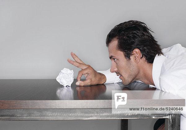 Mann sitzt an Tisch  schiesst mit Papierkugel