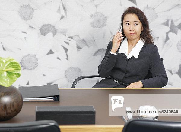 Frau  Asiatin  sitzt an Schreibtisch  telefoniert mit Handy  verärgert