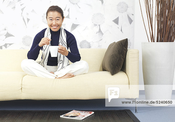 Frau  Asiatin  sitzt im Schneidersitz mit einer Tasse Tee auf Sofa