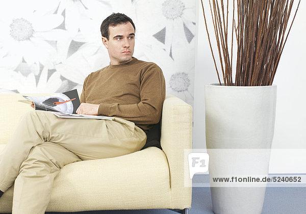 Mann sitzt auf Sofa  liest Zeitschrift