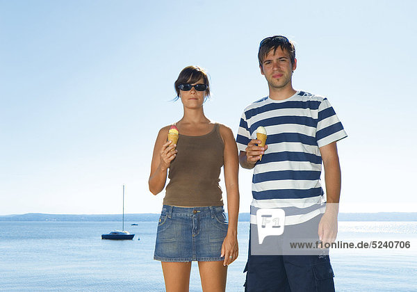 Junges Paar  stehen mit Eistüten an See