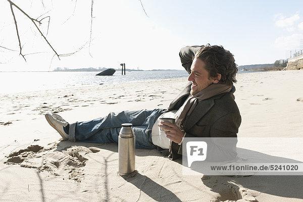 Auf Sand liegender Mann mit Kaffeekanne an der Elbe