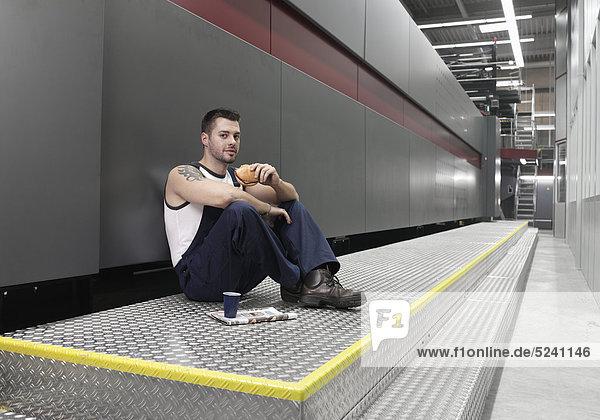Arbeiter sitzt nachdenklich in Druckerei am Boden
