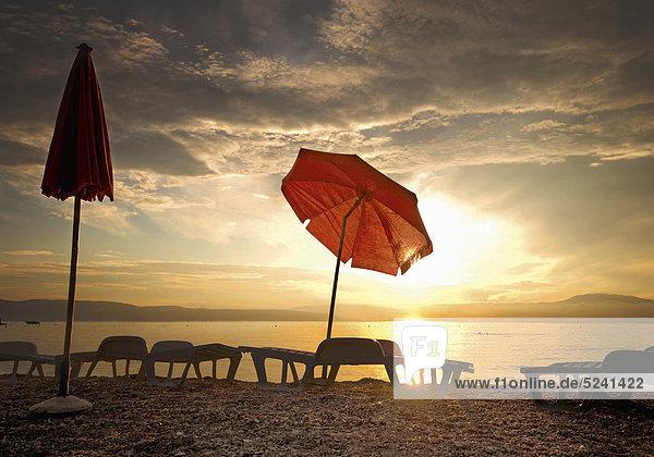 Sonnenschirm und Liegestühle an Strand bei Sonnenuntergang