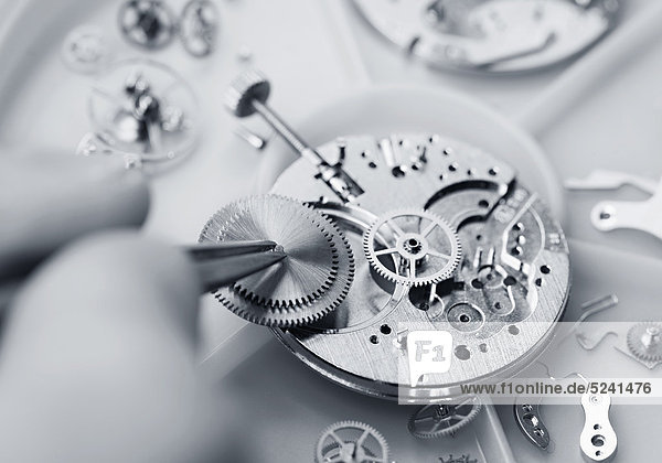 Uhrmacher setzt ein Uhrwerk zusammen