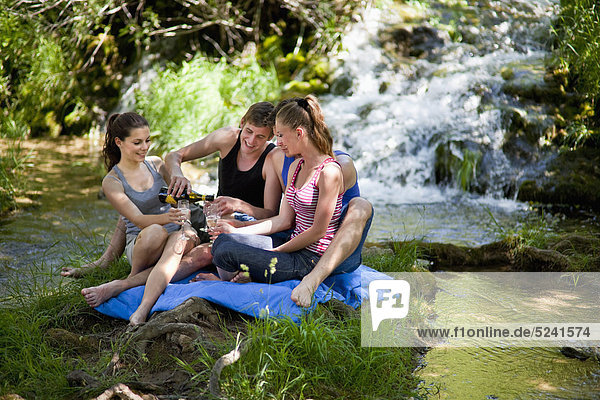 Italien  Toskana  Freunde mit Champagner auf Gras und Picknick