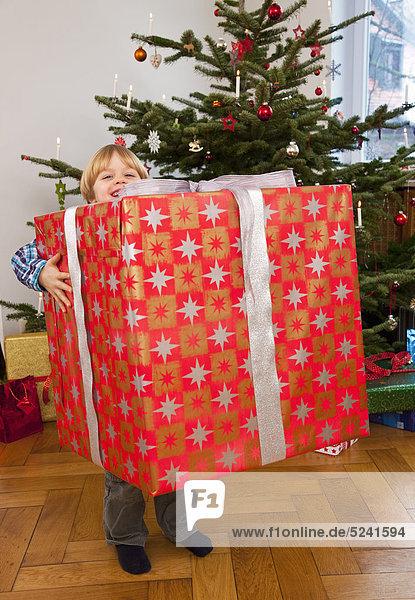 Junge mit großem Weihnachtsgeschenk