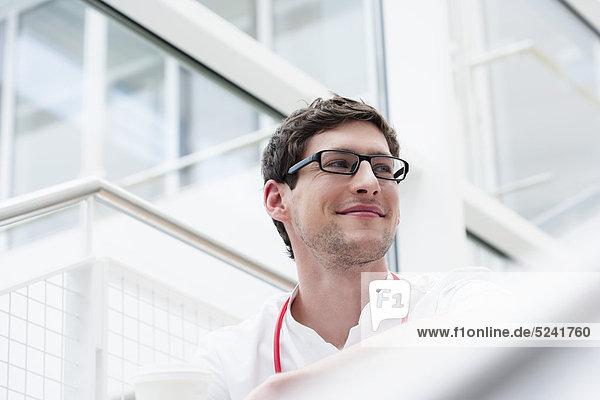 Deutschland  Bayern  Diessen am Ammersee  Junger Arzt mit Brille und Stethoskop  lächelnd