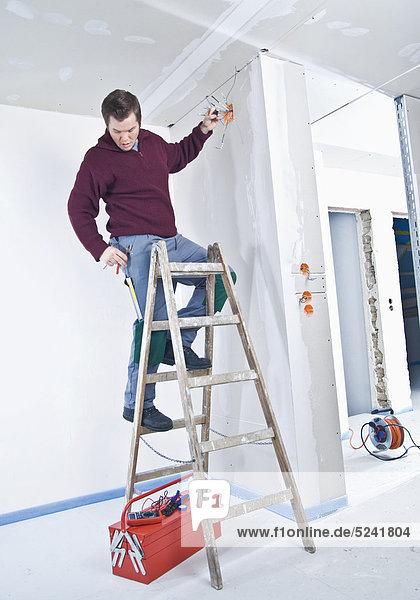 Elektriker steht auf Baustelle auf Leiter