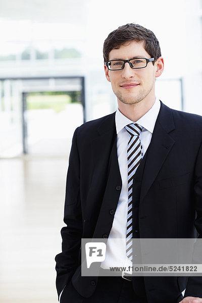 Deutschland  Bayern  Diessen am Ammersee  Geschäftsmann stehend mit Händen in der Tasche  lächelnd  Portrait