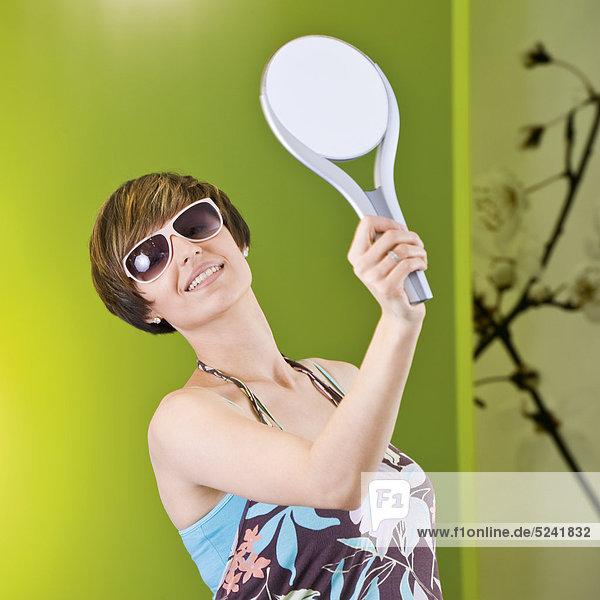 Frau probiert in Boutique Sonnenbrille,  schaut in Handspiegel