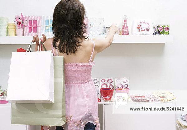 Schwangere Frau mit Einkaufstüten in Boutique an Regal