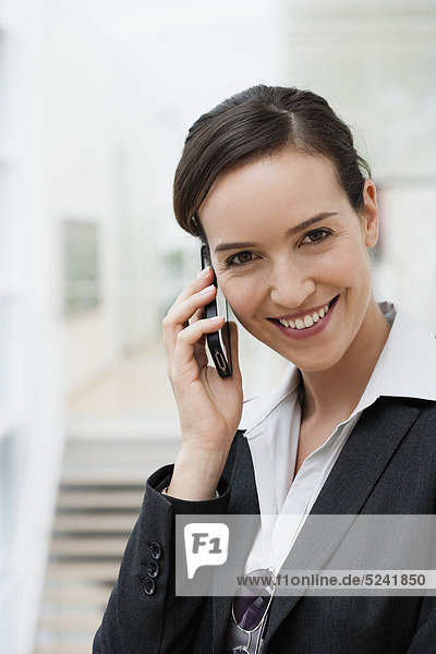 Diessen am Ammersee  Young businesswoman talking on mobile phone  smiling  portrait
