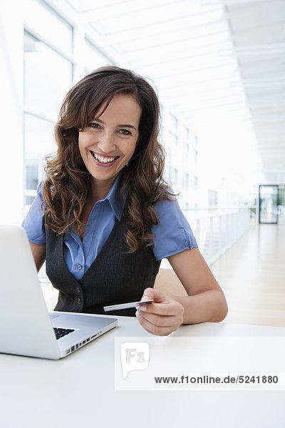 Diessen am Ammersee  Junge Geschäftsfrau mit Laptop und Kreditkarte  lächelnd