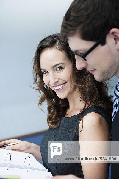 Diessen am Ammersee  Close up of businesswoman holding folderand businessman standing behind  smiling